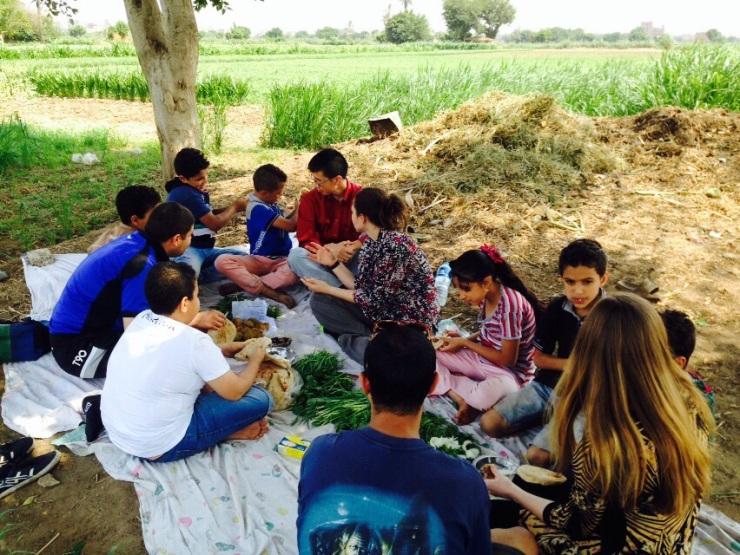 Sharing a lunch of tamaya (falafel), 3sh baladi (bread), with freshly picked basal (onions) and gargeer.